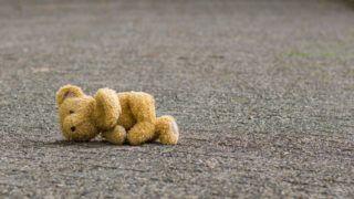 Teddy bear lies on the road