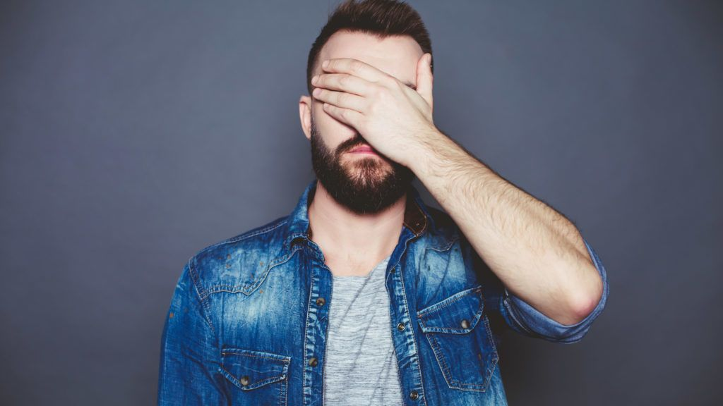 I can not see anything. A young man in a denim shirt closes his eyes with his hand against a gray background.
