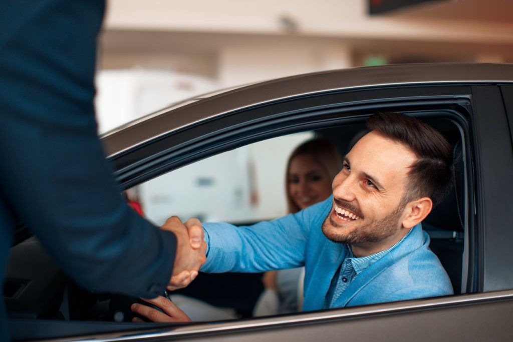 Young couple shaking hands after a successful car buying