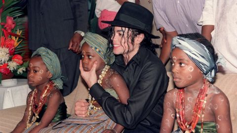 """US pop star and entertainer Michael Jackson sits with orphaned and abandoned Ivory Coast children he invited to the Intercontinental Hotel in Abidjan on Febuary 16, 1992. Michael Jackson died on June 25, 2009 after suffering a cardiac arrest, sending shockwaves sweeping across the world and tributes pouring in on June 26 for the tortured music icon revered as the """"King of Pop."""" AFP PHOTO/Issouf SANOGO (Photo by ISSOUF SANOGO / AFP)"""