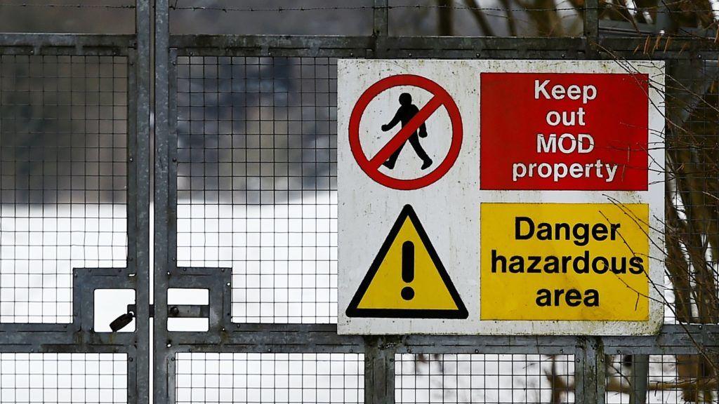 Porton Down, 2018. március 19. Veszélyre és távolságtartásra figyelmeztetõ tábla egy kapun a brit védelmi minisztérium vegyi és biológiai kutatóközpontja területén Porton Downban 2018. március 19-én. A kutatóintézet szakértõinek megállapítása szerint március 4-én a novicsok nevû, oroszországi fejlesztésû, fegyverekben is használható minõségû idegméreg-hatóanyaggal mérgezték meg Szergej Szkripalt, az orosz katonai hírszerzés egykori ezredesét, a brit külsõ hírszerzés (MI6) volt ügynökét és lányát, Julija Szkripalt, akiket azóta is válságos állapotban kezelnek a délnyugat-angliai Salisbury kórházában. A hágai székhelyû Vegyifegyver-tilalmi Szervezet (OPCW) szakértõi ezen a napon érkeznek Nagy-Britanniába. (MTI/EPA/Andy Rain)