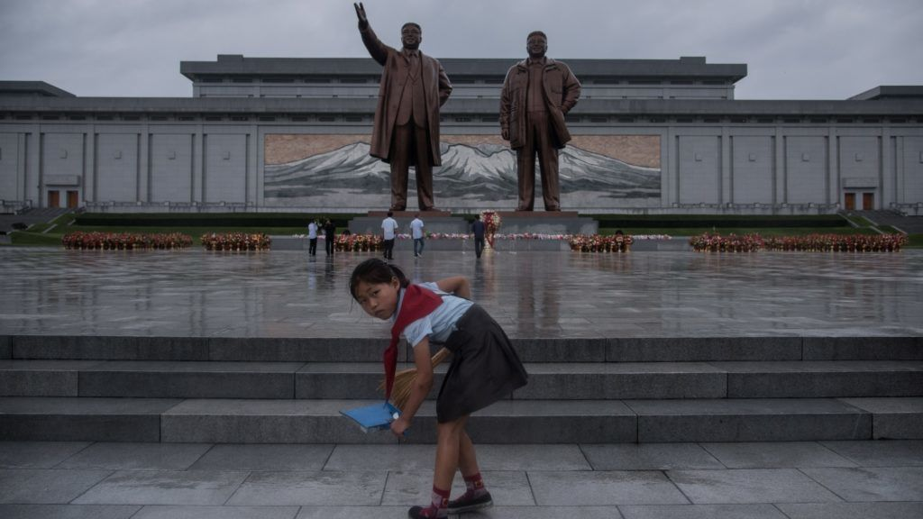 A young girl cleans steps as people bow before the statues of late North Korean leaders Kim Il-Sung (L) and Kim Jong-Il (R) as the country marks 'Victory Day' at Mansu hill in Pyongyang on July 27, 2017. - July 27, which is the 64th anniversary of the signing of the Korean Armistice Agreement, is a public holiday in the nuclear-armed North and celebrated as Victory Day. (Photo by Ed JONES / AFP)