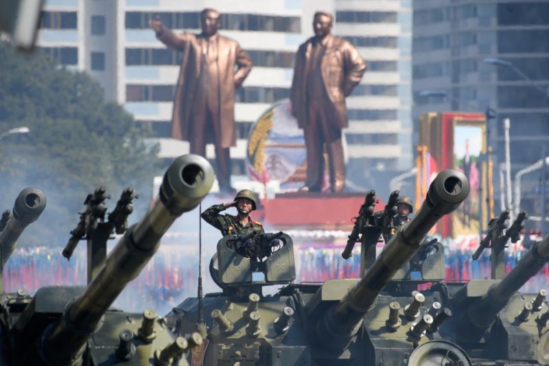 Korean People's Army (KPA) soldiers salute as they ride tanks during a military parade and mass rally on Kim Il Sung square in Pyongyang on September 9, 2018. - North Korea held a military parade to mark its 70th birthday, but refrained from showing off the intercontinental ballistic missiles that have seen it hit with multiple international sanctions. (Photo by Ed JONES / AFP)