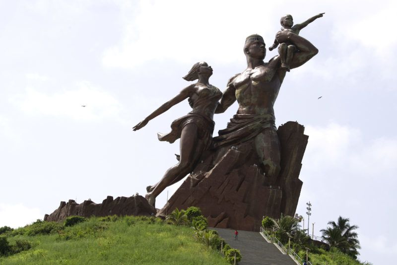 This photograph taken on September 27, 2017, shows The Monument of the African Renaissance which sits on a volcanic hill overlooking Dakar, the capital of Senegal. - The statue is a monumental group of 52 meters in bronze and copper depicting a couple and their child. (Photo by SEYLLOU / AFP)
