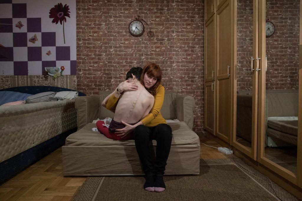 """Mindennapi élet (szorozat) 1. díj ) részlet a sorozatból)Bődey János )Index.hu): """"Ha nekünk mennünk kell, Niki is követni fog minket""""Niki 26 éves, születésétől fogva többszörösen fogyatékos, amit az édesanyja terhessége nyolcadik hónapjában fellépő citomegalovírus okozott. Otthoni és intézményi ápolásra szorul. Önállóan nem tud mozogni, kerekesszékben vagy ágyban tölti ideje nagy részét. Rendszeresen szed gyógyszereket izomgörcs és epilepsziás rohamok ellen. Beszélni nem tud, étkezni is csak segítséggel. Gyakran csikorgatja a fogát.Otthoni ápolását édesanyja és édesapja végzi Budapesten, Magyarországon. Húga, Dóra 1 évre Angliába költözött a jobb megélhetés reményében. Édesanya jelenleg havi 52 800 forint (kb. 185 USD) ápolási díjban részesül havonta, amelyből férje keresete mellett kell megélniük.A Fejlesztő Gondozó Központban sokféleképpen fejlesztik, stimulálják a nappali gondozásban lévőket. Szülei aggódnak a jövő miatt, hogy mi lesz, ha ők már nem lesznek. Azt mondják: """"Ha nekünk menni kell, Niki is követni fog minket""""."""