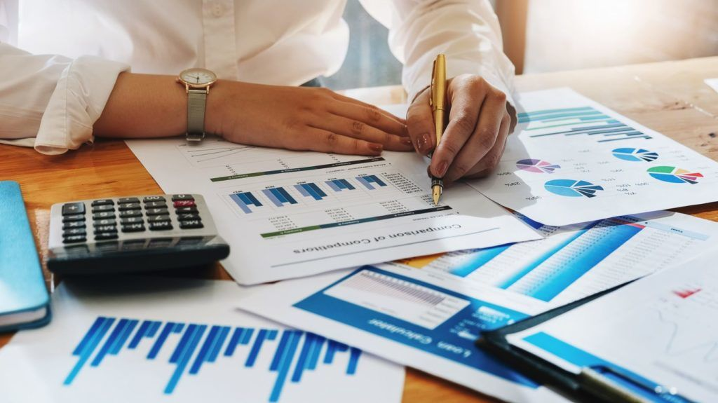 auditor financial or bookkeeper concept , business woman using pen and calculator for audit budget and finance of company on wood desk in office her.