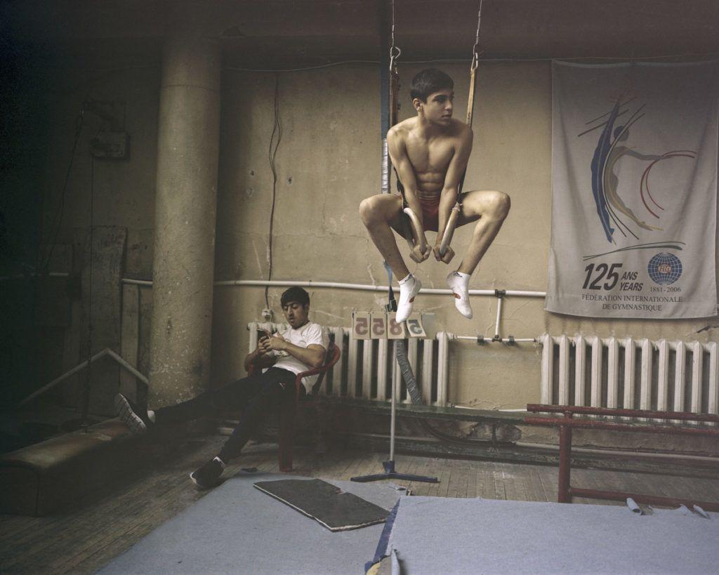 Sport (sorozat) 1. díj (részlet)Zoltai András (szabadfoglalkozású): Az esély – Posztszovjet sportörökség ÖrményországbanAz örmény nép történetének utóbbi 100 éve tele van tragikus mozzanatokkal (népirtás, földrengések, háborúk), és az 1991 óta független Örményország kibontakozását is nemzetközi konfliktusok és gazdasági recesszió nehezítik. Ahogy egykor a szovjet érában, a társadalom perifériáján élő többség számára a sport ma is valós kiugrási lehetőséget kínál. A sokszor ingerszegény környezetben az iskola mellett gyakran a mindennapos edzések jelentik az egyetlen közösségi programot a gyerekek számára. Noha az infrastruktúra és az edzők módszerei legtöbbször a szovjet időket idézi, eltökéltségüket a körülmények nem befolyásolják, mert látják: a bajnokok mindent visznek – busásan megjutalmazzák, és nemzeti hősként ünnepeltetik a sportolókat. A nemzetközi sportsiker az egyéni boldogulás záloga, anyagi és társadalmi megbecsüléssel jár, mivel egy világraszóló eredmény a nemzeti identitást, a méltán híres örmény összetartozás érzését is erősíti.