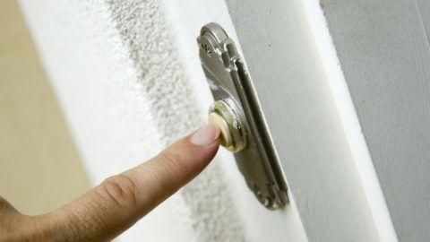 A finger ringing a doorbell.