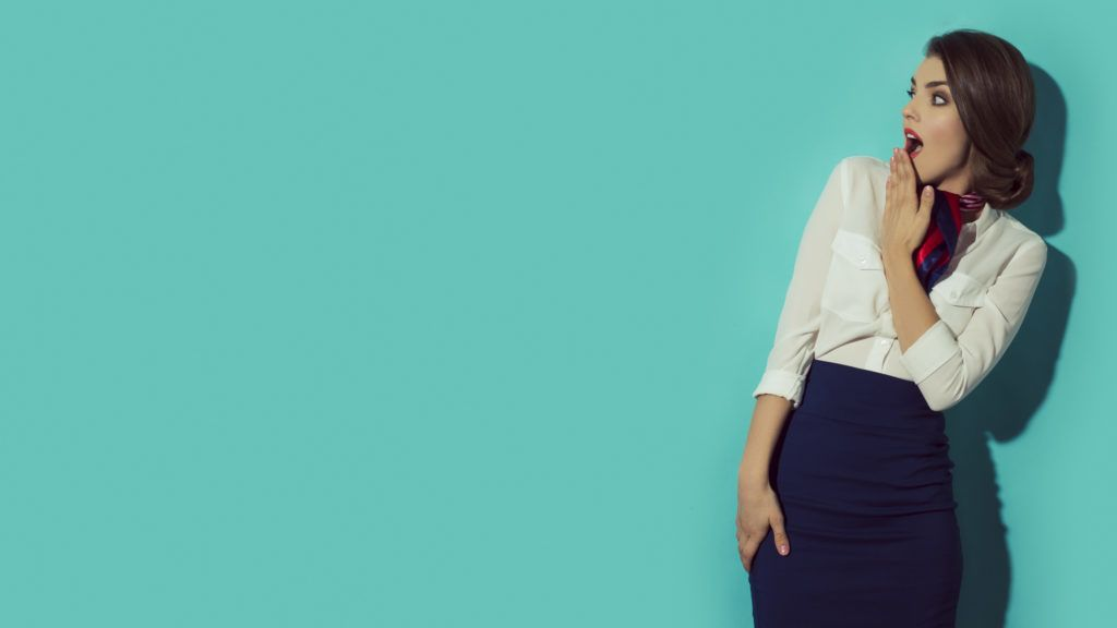 Young suprised woman looking left with her hand beside mouth. Shocked expression. Blue background  in studio