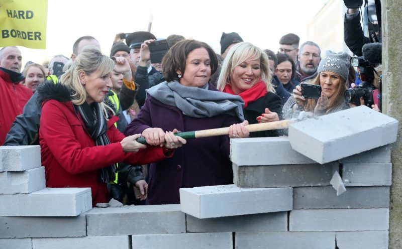 """Sinn Fein republican party president Mary Lou McDonald (C) and Sinn Fein vice-president Michelle O'Neill (R) help to smash doen a mock wall, erected during a demonstration by the anti-brexit campaign group """"Border communities against Brexit"""" on a road crossing the border between Northern Ireland and Ireland in Newry, Northern Ireland, on January 26, 2019. - Keeping the Irish border free-flowing has proved to be the toughest issue to resolve in negotiating Britain's exit from the European Union. The Brexit deal between London and Brussels -- overwhelmingly rejected last week by British MPs -- contains a so-called backstop provision ensuring that if all else fails, the border will remain open. (Photo by Paul FAITH / AFP)"""