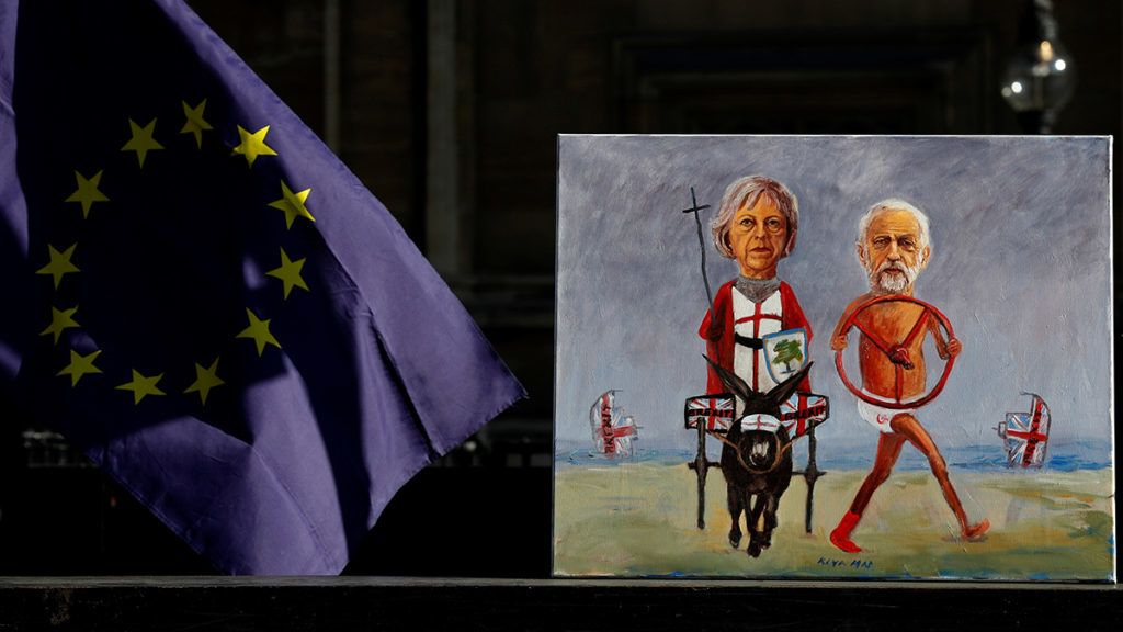 """Political satire artist Kaya Mar poses with an artwork depicting opposition Labour Party leader Jeremy Corbyn (R) and Britain's Prime Minister Theresa May as anti-Brexit activists demonstrate outside of the Houses of Parliament in central London on February 14, 2019. - Prime Minister Theresa May risks another humiliating Brexit defeat at the hands of her own eurosceptic MPs on Thursday, with just weeks to go until Britain officially leaves the EU. Parliament will hold a symbolic vote calling for May to renegotiate her deal's unpopular """"backstop"""" provision and also to rule out leaving the European Union without a deal, as agreed in House of Commons votes last month. (Photo by Adrian DENNIS / AFP)"""
