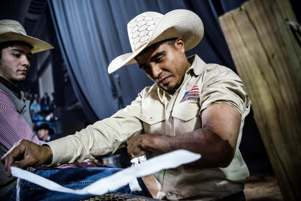 Texas Bullrider Juan Alonzo is pictured taking off wrapping from his arm during the Tuff Hedeman Bull Riding Tour at the El Paso County Colosseum on February 16,2019. Alonzo served five years in the United States Army, practising on wooden bucking barrel while he was deployed in Iraq. - About 25 riders competed for about $30,000 in prize money for this Tuff Hedeman Bull Riding Tour stage named after the four time bull riding world champion who grew up in El Paso, Texas. (Photo by PAUL RATJE / AFP)