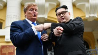 US President Donald Trump impersonator Russel White (L) and North Korean leader Kim Jong Un impersonator Howard X (R) pose together for photographs outside the Opera House in Hanoi on February 22, 2019. (Photo by Manan VATSYAYANA / AFP)