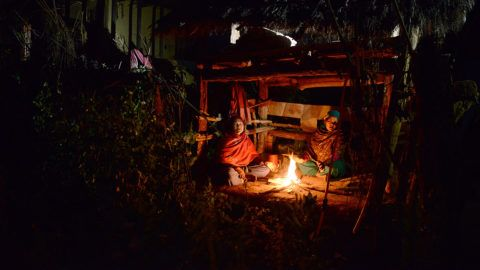 In this photograph taken on February 3, 2017, Nepalese women Pabitra Giri (L) and Yum Kumari Giri (R) sit by a fire as they live in a Chhaupadi hut during their menstruation period in Surkhet District, some 520km west of Kathmandu. - The practice of banning women from the home when they are menstruating is linked to Hinduism and considers women untouchable at this time. They are banished from the home -- barred from touching food, religious icons, cattle and men -- and forced into a monthly exile sleeping in basic huts. Chhaupadi was banned a decade ago, but new legislation currently before parliament will criminalise the practice, making it a jailable offence to force a women to follow the ritual. (Photo by PRAKASH MATHEMA / AFP) / TO GO WITH AFP STORY: Nepal-women-religion-society, FEATURE by Annabel SYMINGTON