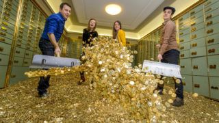 """(L to R) Members of """"Generation Basic Income"""" Daniel Haeni, Pola Rapatt, Marilola Wili and Che Wagner pose with eight million coins of Swiss five-cent in a vault on December 3, 2013 in Basel, inside a bank safe that will both go on sale on a luxury website. The 15 tons coins were dumped by a truck last october in front of the Swiss house of Parliament in a symbolic gesture when the activists submitted over 130,000 signatures to organize a nationwide referendum guaranteeing all Swiss nationals a basic income of CHF 2,500 a month (2,700 USD). AFP PHOTO / FABRICE COFFRINI (Photo by FABRICE COFFRINI / AFP)"""