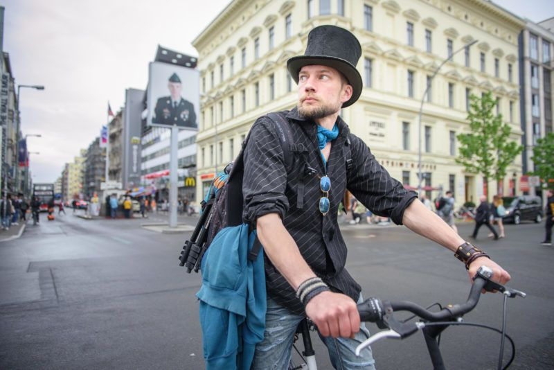 23 April 2018, Germany, Berlin: Juha Jaervinen, participant of the experiment Basic Income in Finland, rides past Checkpoint Charlie on a rented bike. Photo: Gregor Fischer/dpa