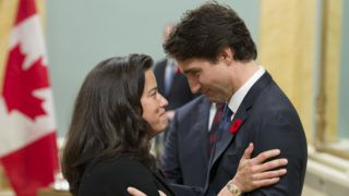 """(FILES) In this file photo taken on November 4, 2015 Canadian Prime Minister Justin Trudeau speaks with Minister of Justice Jody Wilson-Raybould during a swearing-in ceremony at Rideau Hall, in Ottawa. - Canada's former attorney general resigned from Prime Minister Justin Trudeau's cabinet on February 12, 2019 amid controversy over the prosecution of construction and engineering firm SNC-Lavalin. """"With a heavy heart, I have submitted my letter of resignation to the prime minister as a member of cabinet,"""" Jody Wilson-Raybould said in a Twitter message. Wilson-Raybould had been the nation's first indigenous attorney general and justice minister until last month when she was shuffled to the veterans affairs portfolio, ahead of October elections. (Photo by ADRIAN WYLD / POOL / AFP)"""