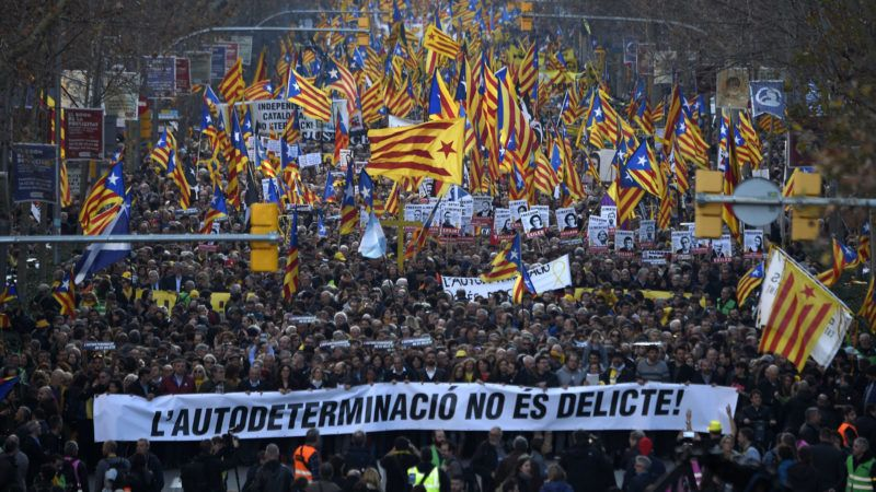 """Demonstrators hold a banner reading """"Self-determination is not a crime"""" and wave Catalan pro-independence Estelada flags during a protest against the trial of former Catalan separatist leaders in Barcelona on February 16, 2019. - Twelve Catalan separatist politicians and activists face years behind bars if they are convicted of rebellion or other charges for pushing an independence referendum in October 2017, in defiance of a court ban, and a brief declaration of independence. (Photo by LLUIS GENE / AFP)"""