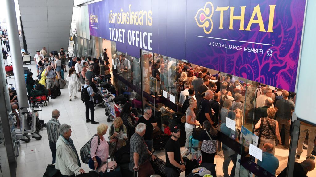Stranded passengers wait the Thai Airways ticket counter at the Suvarnabhumi International Airport in Bangkok on February 28, 2019. - Thai airways cancelled 11 European-bound flights after Pakistan closed its airspace as tensions with India mount, the carrier said February 28, a move affecting thousands of passengers at the height of the country's busy tourist season. (Photo by Lillian SUWANRUMPHA / AFP)