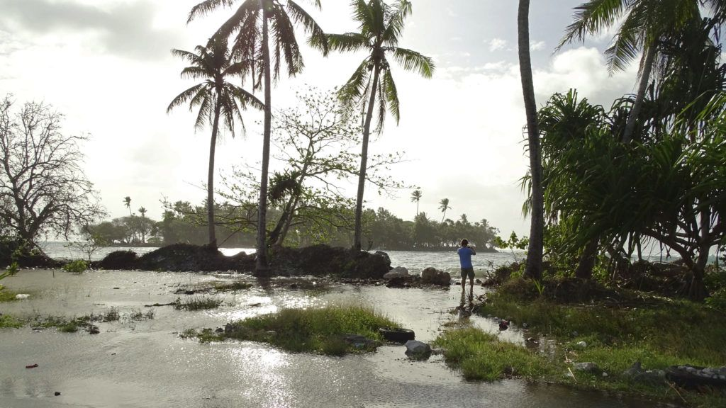 In this photo taken on March 9, 2016, a resident walks through tidal water in Majuro Atoll, in the Marshall Islands. - Residents in low-lying areas of the Marshall Islands were braced for ongoing flooding on March 11, as a series of inundations underscored the Pacific island nation's vulnerability to climate change. (Photo by HILARY HOSIA / AFP)