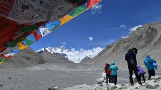 --FILE--Tourists are pictured beside the Buddhist prayer flags provided by local villagers to help tourists string them along mountain ridges and make wishes at the foot of the Mount Everest (Qomolangma) in southwest China's Tibet Autonomous Region, 16 June 2017.  Mount Qomolangma National Nature Reserve in China's Tibet Autonomous Region has banned ordinary tourists from entering its core zone to better conserve the environment of the world's highest mountain. But for travelers who have a climbing permit, the mountaineering activities will not be affected, according to the reserve which was set up in 1988.