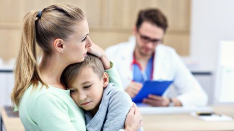 Picture showing little boy with his mother in clinic being examined by pediatrician