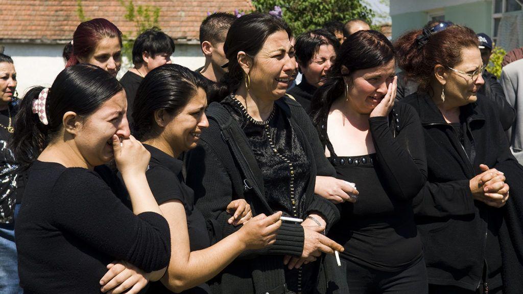Tiszalök, 2009. április 27.Az áldozat felesége (k), valamint családtagok és barátok állnak sírva a 2009. április 22-én agyonlőtt 54 éves, roma származású Kóka Jenő holttestét szállító halottaskocsi mellett a Szabolcs-Szatmár-Bereg megyei Tiszalök-Újtelepen, mielőtt a helyi temető ravatalozójába kísérik. A férfit április 29-én kora délután kísérik utolsó útjára.MTI Fotó: Balázs Attila