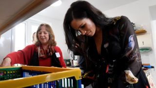 BRISTOL, ENGLAND - FEBRUARY 01: Meghan, Duchess of Sussex prepares food parcels to go in the charity outreach van and writes personalised messages on fruit in the charity kitchen, next to volunteer Sue Creighton, during a visit to One25, a charity specialising in helping women to break free from street sex work, addiction and other life-controlling issues, on February 1, 2019 in Bristol, England. (Photo by Toby Melville - WPA Pool/Getty Images)