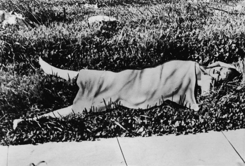 The naked corpse of American aspiring actress and murder victim Elizabeth Short (1924 - 1947), known as the 'Black Dahlia,' lies on a grassy field covered by a blanket after the body was discovered in a vacant lot in the Leimert Park neighborhood of Los Angeles, California, January 15, 1947. Short's murdered body was severly mutilated and severed at the waist. The murder still remains unsolved. (Photo by INTERNATIONAL NEWS PHOTO/Getty Images)
