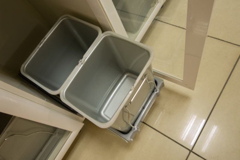 Two grey rubber (dirty) trash cans filled to the top. Rain drops covering the bags.