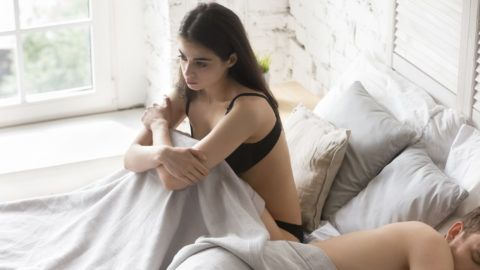 Sad young girlfriend sitting in bed thinking about relationship problems, thoughtful upset woman considering breaking up with boyfriend, girl consider man indifference or sexual troubles with lover