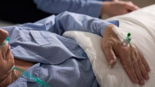 Close-up of terminally ill man's hand with drip