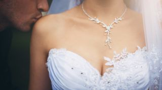 Close-up of female breasts in the low-necked dress and the groom kissing a bride's shoulder.