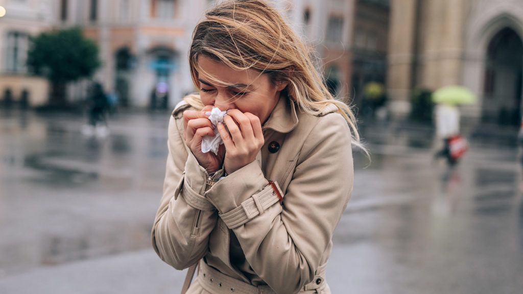 A beautiful young woman blowing her nose in public.