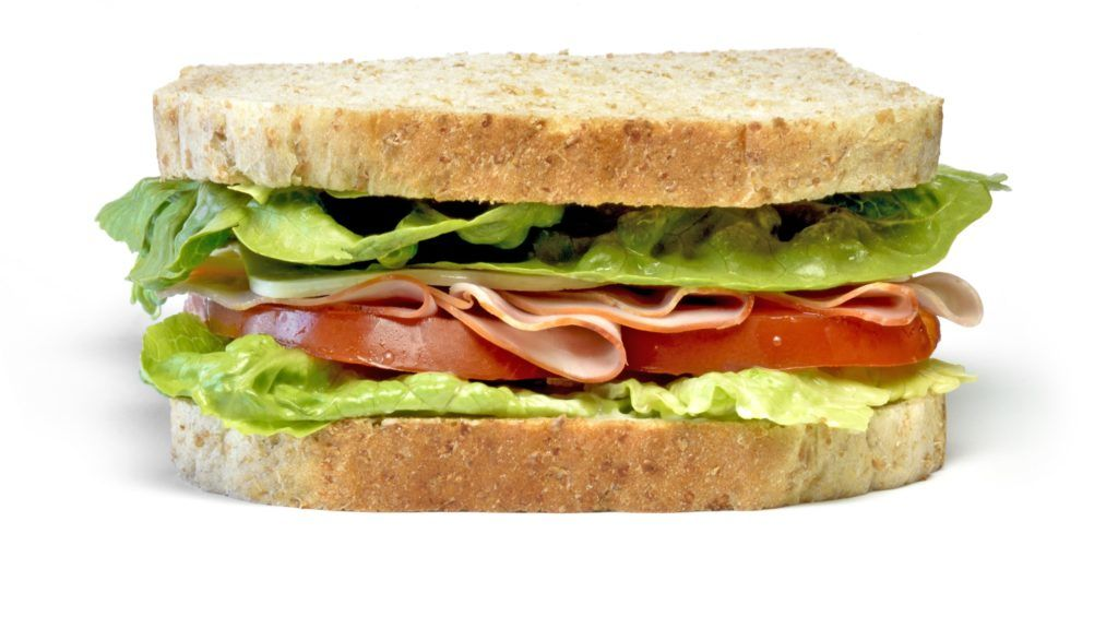 Delicious ham and cheese sandwich, isolated on white background. Gourmet toast or sandwich with lettuce, tomato, chess and turkey. Whole grain sandwich, healthy eating.