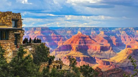 Grand Canyon South Rim view  at golden hour under stormy sky with tourists at lookout point taking pictures and selfies