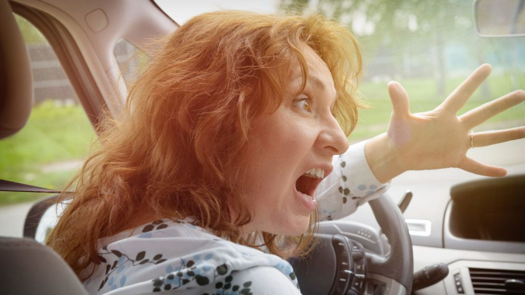 Angry woman driver screaming and gesturing while driving a car. Negative human emotions concept
