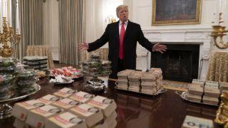Washington, 2019. január 15. Donald Trump amerikai elnök a gyorséttermi ételekkel teli asztalról beszél riportereknek a washingtoni Fehér Ház reprezentatív ebédlõjében, ahol az egyetemi amerikaifutball-bajnokságban gyõztes Clemson Tigers csapatának tiszteletére ad fogadást 2019. január 14-én. Trump saját maga fizette hamburgerrel, pizzával és más gyorséttermi finomságokkal látta vendégül a sportolókat, mert a több mint három hete tartó részleges kormányzati leállás miatt a fehér házi személyzet tagjainak többsége szabadságon van. MTI/EPA/Chris Kleponis
