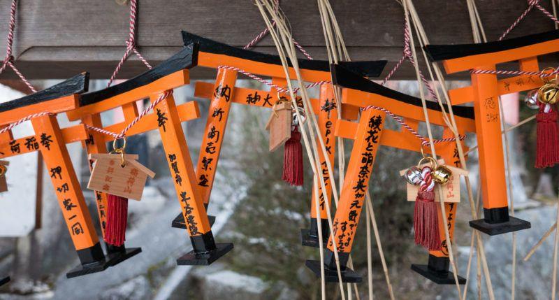 Kyoto, Japan - February 22, 2017 - Ema (wooden prayer plaques) shaped like miniature torii hang at a small shrine on Mt. Inari.