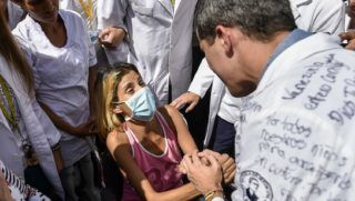 """Opposition leader and self-proclaimed """"acting president"""" Juan Guaido (R), greets a patient outside the University Hospital of Venezuela's Central University (UCV) in Caracas, during a protest he convened against the government of President Nicolas Maduro, on January 30, 2019. - Venezuelan President Nicolas Maduro hit out Wednesday at military """"mercenaries"""" he says are conspiring to divide the armed forces and plot a coup as the opposition planned a new protest to force the socialist leader from power. (Photo by Luis ROBAYO / AFP)"""