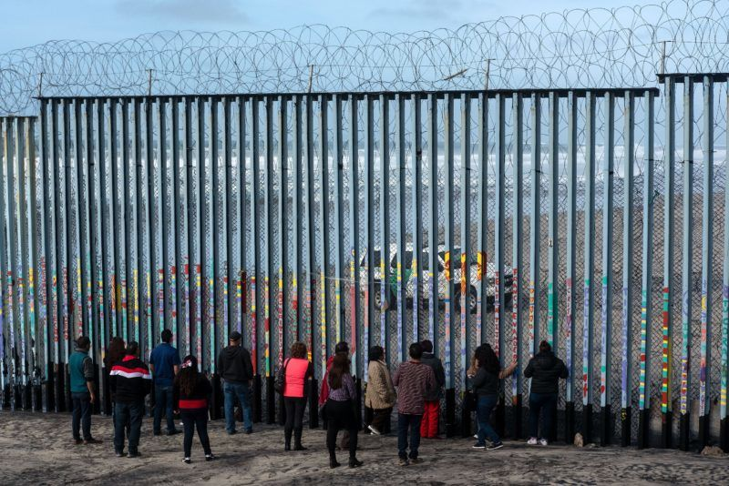 People look at US border patrol guards through the US-Mexico border fence, in Tijuana, in Baja California State, Mexico, on January 18, 2019. - A new caravan of Central American migrants trying to reach the United States made its way across Guatemala Thursday, with the first members crossing into southern Mexico. (Photo by Guillermo Arias / AFP)