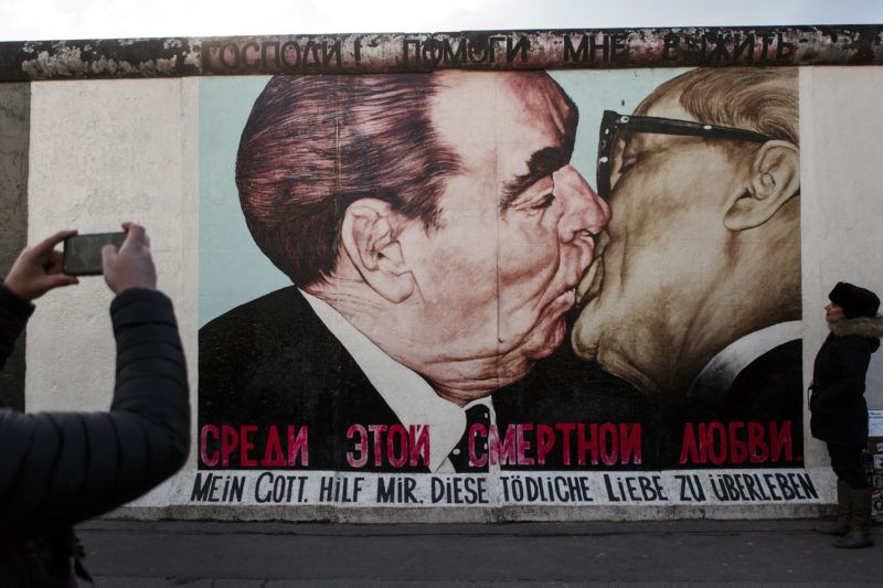 BERLIN, GERMANY - FEBRUARY 05: Visitors stand in front of a mural depicting former Soviet leader Leonid Brezhnev kissing former communist East German leader Erich Honecker at the East Side Gallery, which is a surviving remnant of the Berlin Wall, on February 5, 2018 in Berlin, Germany. Today has been 10,316 days since the Berlin Wall officially fell, the same number of days that it stood between 1961 and 1989. The Berlin Wall, built by the communist authorities of East Germany, divided capitalist West Berlin from communist East Berlin and came to symbolize the Cold War between the western Allies, led by the United States, and the Eastern Bloc, led by the Soviet Union. (Photo by Carsten Koall/Getty Images)