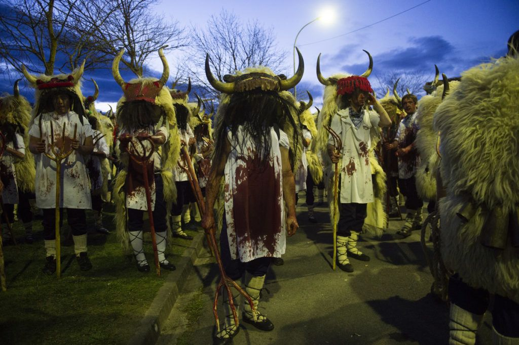Participants covered in cow blood and wearing Momotxorro costumes take part in the Alsasua carnival in the northern Spanish village of Alsasua, in Navarra province, on March 5, 2019. - During the traditional Alsasua carnival local residents cover their clothes, arms and face with cow blood and parade in the village. (Photo by ANDER GILLENEA / AFP)