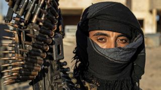 """A fighter with the Syrian Democratic Forces (SDF) is pictured in the town of Baghouz, on the frontline of fighting to expel the Islamic State group from the area, in the eastern Syrian province of Deir Ezzor, on March 12, 2019. - US-backed forces said the Islamic State group was living its """"final moments"""" after thunderous shelling on its last scrap of land in eastern Syria prompted 3,000 jihadists to surrender. But the die-hard IS fighters who stayed to defend the remnants of their """"caliphate"""" struck back with a wave of suicide bombings, according to the Kurdish-led Syrian Democratic Forces. (Photo by Delil SOULEIMAN / AFP)"""