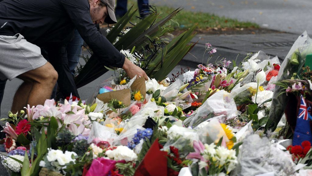 People present floral tributes at a makeshift memorial for victims of the March 15 mosque attacks, in Christchurch on March 17, 2019. - The death toll from horrifying shootings at two mosques in New Zealand rose to 50, police said March 17, as Christchurch residents flocked to memorial sites and churches across the city to lay flowers and mourn the victims. (Photo by Tessa BURROWS / AFP)