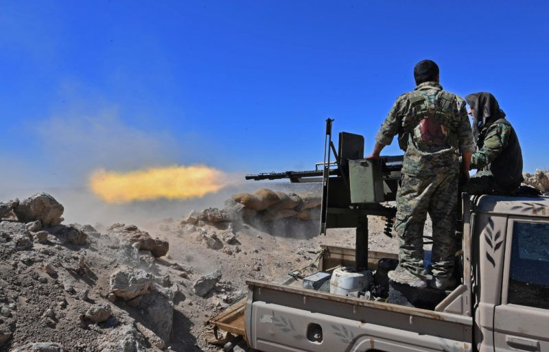 A fighter with the Syrian Democratic Forces (SDF) fires a truck-mounted gun toward a part of Baghouz where remaining Islamic State (IS) group fighters are holding out in their last position, in the countryside of the eastern Syrian province of Deir Ezzor on March 18, 2019. - A shroud of black smoke covered the Islamic State group's last Syria redoubt today as US-backed forces battled holdout jihadists after a night of shelling and heavy air strikes. The Kurdish-led SDF have been closing in on IS fighters holed up in a small sliver of territory in the village of Baghouz in eastern Syria since January. (Photo by GIUSEPPE CACACE / AFP)