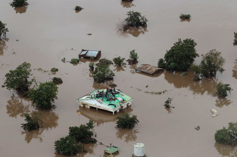 """This handout picture taken and released on March 18, 2019, by the Mission Aviation Fellowship shows people on a roof surrounded by flooding in an area affected by Cyclone Idai in Beira. - A cyclone that ripped across  Mozambique and Zimbabwe has killed at least 162 people with scores more missing and caused """"massive and horrifying"""" destruction in the Mozambican city of Beira, authorities and the Red Cross said on March 18, 2019. Cyclone Idai tore into the centre of Mozambique on the night of March 14 before barreling on to neighbouring Zimbabwe, bringing flash floods and ferocious winds, and washing away roads and houses. The Red Cross said 90 percent of Beira and its surrounds are """"damaged or destroyed"""". (Photo by Rick Emenaket / Mission Aviation Fellowship / AFP) / RESTRICTED TO EDITORIAL USE - MANDATORY CREDIT """"AFP PHOTO / MISSION AVIATION FELLOWSHIP / RICK EMENAKET"""" - NO MARKETING NO ADVERTISING CAMPAIGNS - DISTRIBUTED AS A SERVICE TO CLIENTS --- NO ARCHIVE ---"""