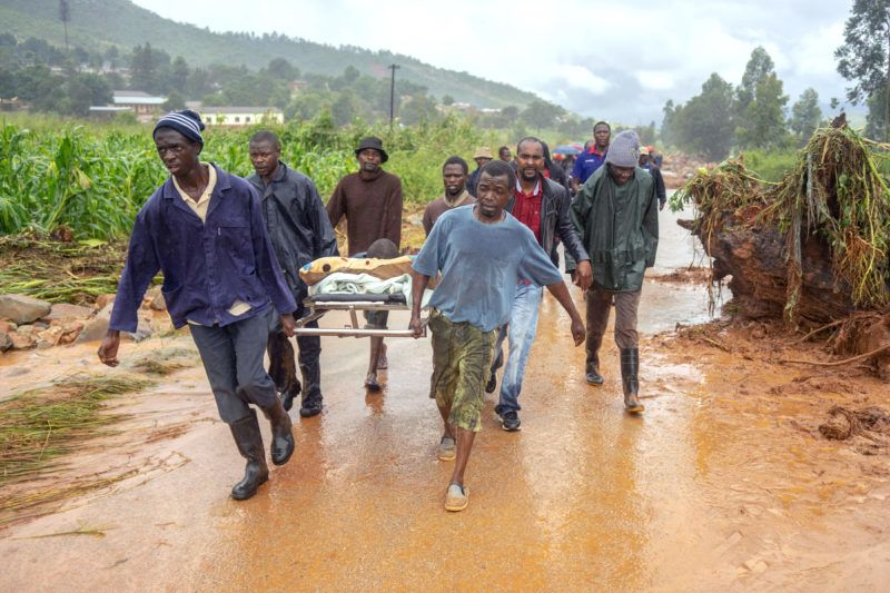 A rescued man is seen carried on a stretcher bed by friends on March 18, 2019, in Ngangu township, Chimanimani, eastern Zimbabwe, after the area was hit by the cyclone Idai. - A cyclone that ripped across Mozambique and Zimbabwe has killed at least 162 people with scores more missing. Cyclone Idai tore into the centre of Mozambique on the night of March 14 before barreling on to neighbouring Zimbabwe, bringing flash floods and ferocious winds, and washing away roads and houses. (Photo by Zinyange AUNTONY / AFP)
