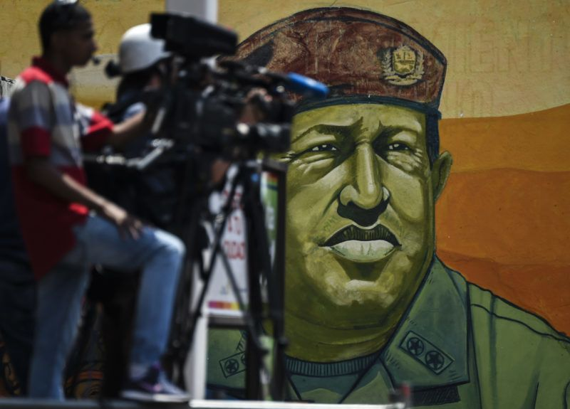 A mural of late Venezuelan President Hugo Chavez is seen during a pro-government rally in Caracas on March 23, 2019. - It is two months since Juan Guaido has asserted he is Venezuela's interim president. Domestically, he has been unable to shake President Nicolas Maduro from power. (Photo by Juan BARRETO / AFP)