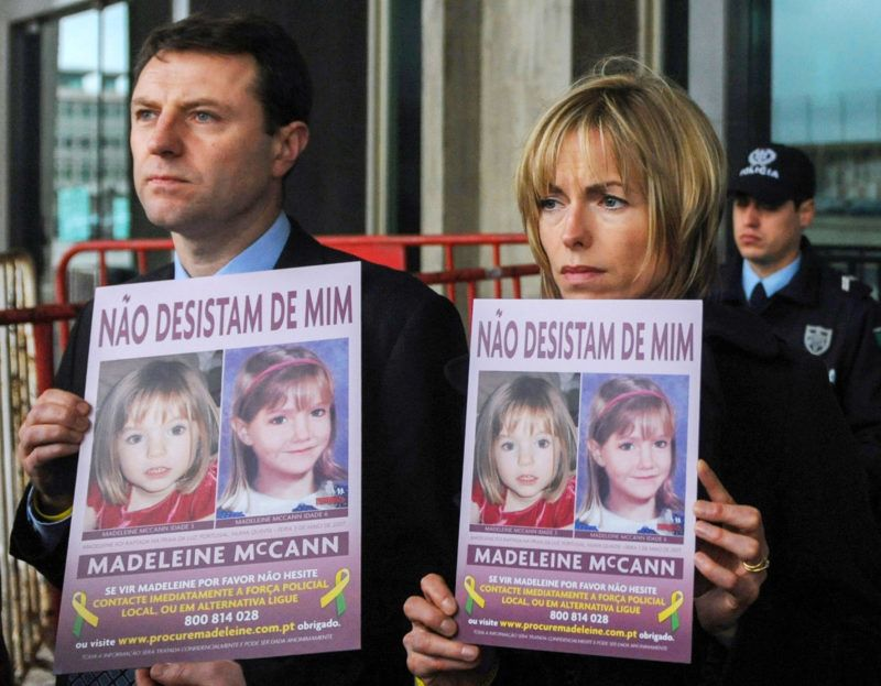 """Gerry (L) and Kate McCann pose with boards portraiting their missing daughter Madeleine reading """"don't give me up"""" as they leave the Tribunal Civil de Lisboa in Lisbon on February 10, 2010, after the last court session of their libel action against Goncalo Amaral the Portuguese police officer who led the initial probe in the case. Amaral, who has been on trial over claims he made in a book and a documentary that Gerry and Kate McCann were involved in their daughter Madeleine's disappearance, has been ordered to pay hundreds of thousands of pounds to the McCann family following a libel case in a Portuguese court. In a written verdict, a Lisbon court agreed that Amaral should pay Mr and Mrs McCann 250,000 euros (Ł179,000) each in damages and it banned further sales of his book The Truth Of The Lie.  AFP PHOTO/ FRANCISCO LEONG (Photo by FRANCISCO LEONG / AFP)"""